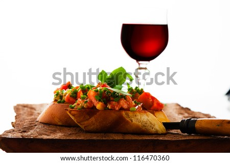 delicious bruschetta appetizer with red wine glass on wooden board - stock photo