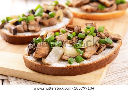 Delicious bruschetta with mushrooms on cutting board on table close-up