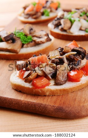 Delicious bruschetta with mushrooms on cutting board on table close-up - stock photo