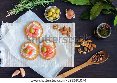 Delicious bruschetta with prosciutto and olives on background of olive oil with spices, rosemary, garlic, Bay leaf, nuts and wooden spoon with pepper. Italian appetizer. Top view.  - stock photo