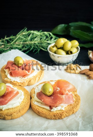 Delicious bruschetta with prosciutto and olives on background of rosemary, garlic, Bay leaf and nuts. Italian appetizer. Selective focus. Vertical. - stock photo