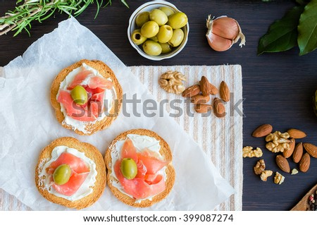 Delicious bruschetta with prosciutto and olives on background of rosemary, garlic, Bay leaf and nuts. Italian appetizer. Top view.  - stock photo