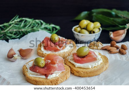 Delicious bruschetta with prosciutto and olives on background of rosemary, garlic, Bay leaf and nuts. Italian appetizer. Selective focus. - stock photo