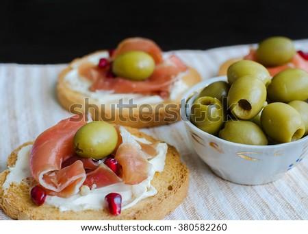 Delicious bruschetta with prosciutto, olives and pomegranate. Italian bruschetta sandwich. Close Up. Italian appetizer. Selective focus. - stock photo