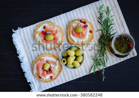 Delicious bruschetta with prosciutto, olives and pomegranate on background of olive oil with spices and rosemary. Italian bruschetta sandwich. Italian appetizer. Top view. - stock photo