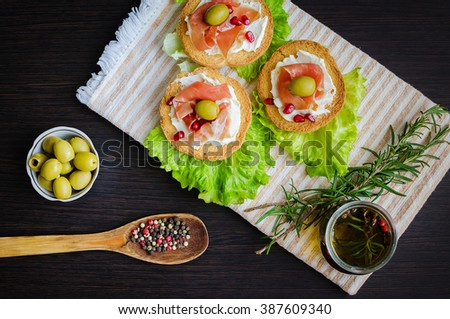 Delicious bruschetta with prosciutto, olives and pomegranate on background of olive oil with spices, rosemary and wooden spoon with pepper. Italian appetizer. Top view. - stock photo