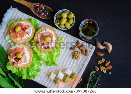 Delicious bruschetta with prosciutto, olives and pomegranate on dark background with olive oil with spices, rosemary, Bay leaf, garlic, nuts and wooden spoon with pepper. Italian appetizer. Top view. - stock photo