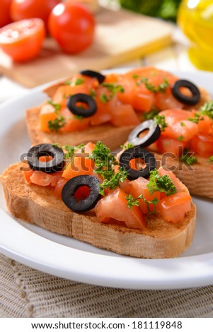 Delicious bruschetta with tomatoes on plate on table close-up - stock photo