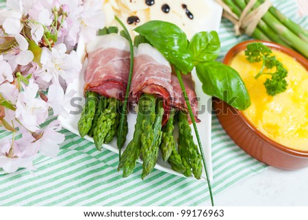 Delicious bunch of asparagus rolled with speck