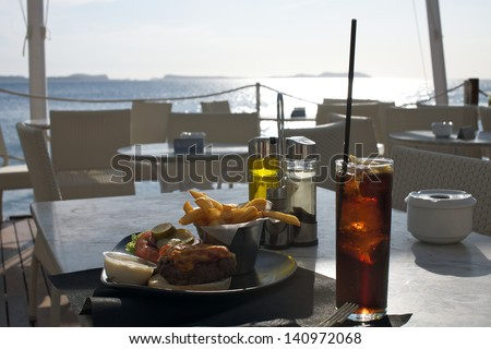Delicious burger and a glass of cola on a table, with a beautiful sea view in the background - stock photo