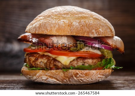 Delicious burger on wooden board - stock photo
