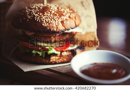 Delicious burger with pork steak, tomato, cucumber and fresh salad grilled and put between two bagels with sesame seeds. Unhealthy but so tasty fast food. Close up photo in macro mode - stock photo