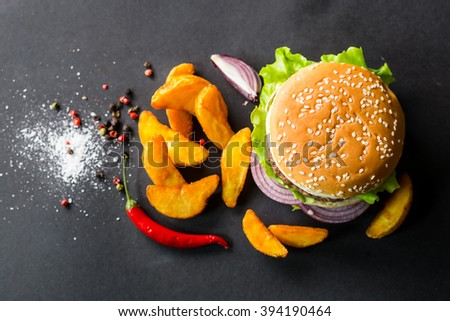 Delicious burgers and fries on a black background. View from above - stock photo