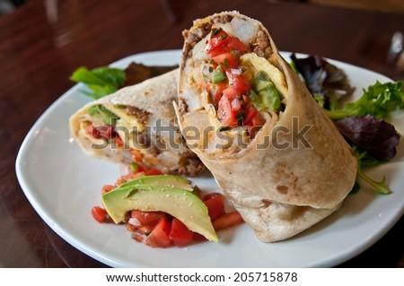 Delicious burrito brunch cut in half on white plate - stock photo