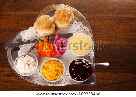 Delicious butter scones on a silver heart shaped tray served with roses cheese cream and jam preserves on a wooden table. Image contains copy space. - stock photo