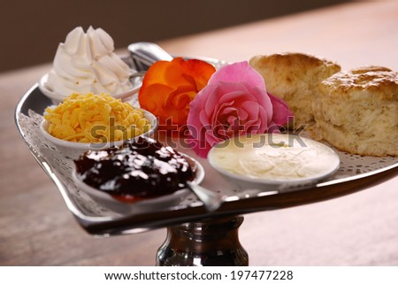 Delicious butter scones on a silver heart shaped tray served with roses cheese cream and jam preserves on a wooden table. - stock photo
