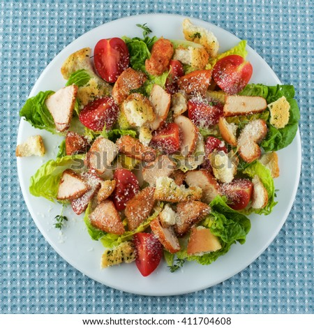 Delicious Caesar Salad with Roasted Chicken Breast, Garlic Crouton, Romaine Lettuce, Cherry Tomatoes and Grated Parmesan Cheese closeup on White Plate. Top View on Blue Napkin - stock photo