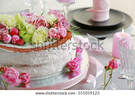 Delicious cake decorated with flowers on blurred background