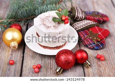 Delicious cake on saucer with holly and berry on Christmas decoration and wooden background - stock photo