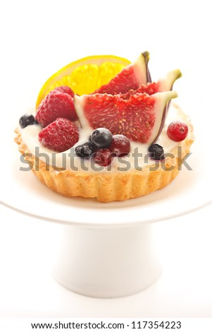 Delicious cake with custard and fresh berries and fruits on a cake stand.