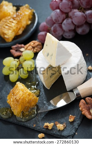 delicious Camembert with fresh honey, grapes and nuts on a dark background, top view, vertical