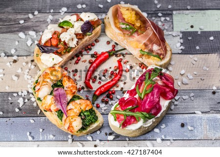 Delicious Canapes.Plate of assorted Italian appetizer bruschetta with chopped vegetables, salmon and meat on ciabatta bread, garnished with green mix salad - stock photo