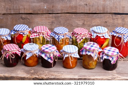 Delicious canned food for the winter. Glass jars with fruits and vegetables are on the vintage board. - stock photo