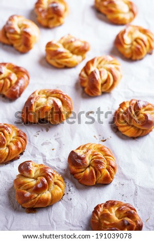 Delicious cardamom roll close-up on white oven paper - stock photo