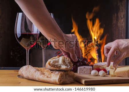 delicious cheese and wine at the fireplace - stock photo