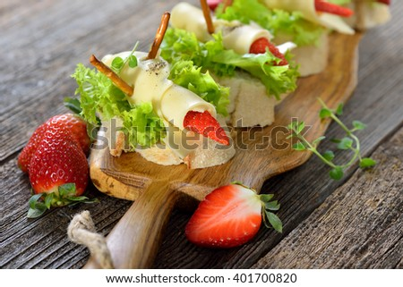 Delicious cheese rolls with strawberries on Italian ciabatta bread with lettuce leaves - stock photo