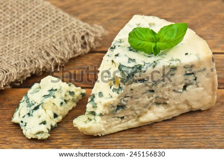 delicious cheese with mold and basil leaves - stock photo