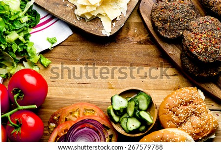 Delicious cheeseburger ingredients a juicy beef patty, cheese, fresh lettuce, onion, tomato, pickles and a  fresh bun with sesame seeds presented on a wooden cutting board with copyspace - stock photo