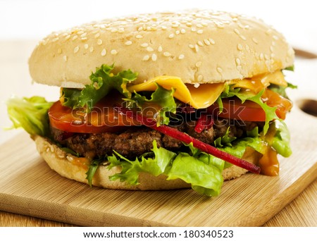 Delicious cheeseburger with beef, cheese, fresh lettuce, onion and tomato on a fresh bun with sesame seed