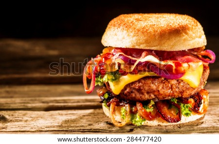 Delicious cheeseburger with salad ingredients on a grilled beef patty served on a crusty golden bread roll on a rustic wooden table with copyspace - stock photo