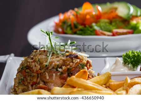 delicious chicken fried rice prepared and presented restaurant style with fresh ingredients and served with a side salad - stock photo