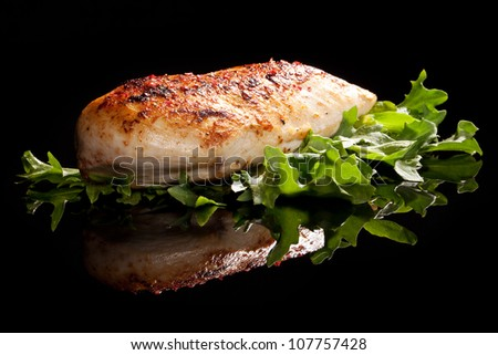 Delicious chicken steak with green fresh lettuce isolated on black background with reflection. Luxury food concept. - stock photo