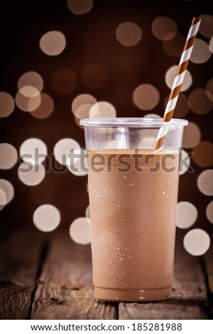 Delicious chilled takeaway chocolate milkshake in a plastic glass standing on a rustic wooden table against a backdrop bokeh of twinkling festive lights - stock photo