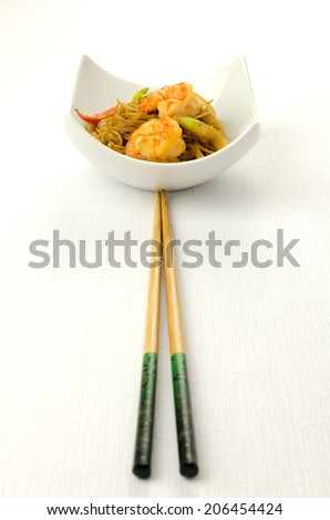 Delicious Chinese noodles topped with shrimps served in a stylish contemporary white porcelain bowl with chopsticks for healthy seafood cuisine, studio shot on white - stock photo
