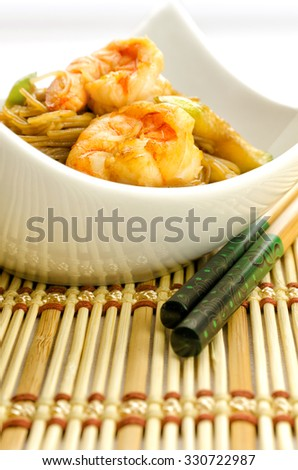 Delicious Chinese noodles topped with shrimps served in a stylish contemporary white porcelain bowl with chopsticks for healthy seafood cuisine, studio shot on white