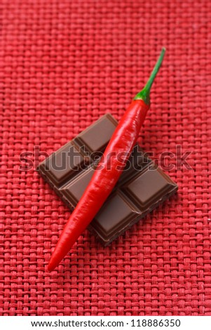 Delicious chocolate and red hot chili on a wicker background.