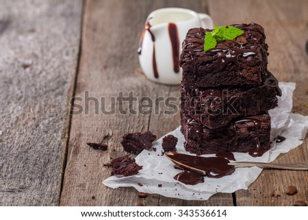 Delicious chocolate brownie with mint on wooden table. - stock photo
