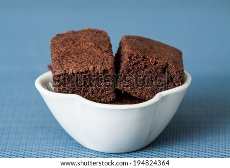 Delicious chocolate brownies in a bowl, blue background.
