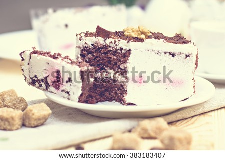 Delicious chocolate cake on plate on table on light background. Tonned photo.