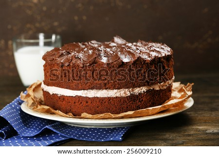 Delicious chocolate cake on table on brown background - stock photo