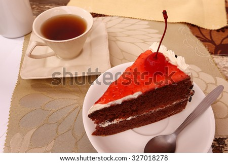 Delicious chocolate cake,tea cup,red strawberry jam topping red cherry - stock photo