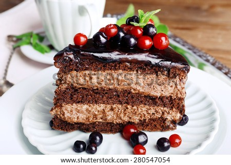 Delicious chocolate cake with berries on plate on table close up - stock photo