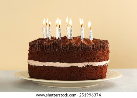 Delicious chocolate cake with candles on table on light background - stock photo