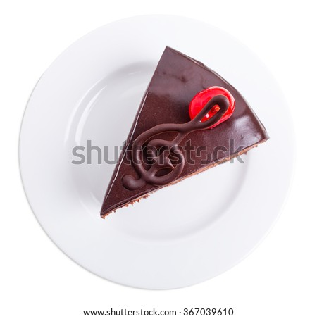 Delicious chocolate cake with cocktail cherry and musical note on top. Isolated on a white background. - stock photo