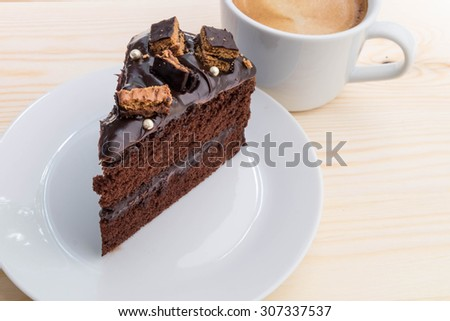 Delicious chocolate cake with coffee on plate on table wood background