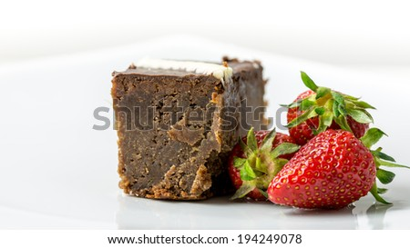 Delicious chocolate cake with fresh juicy red strawberries. - stock photo